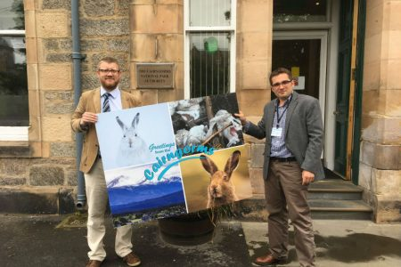 OneKind presents Cairngorms with a giant postcard calling for an end to mountain hare culls